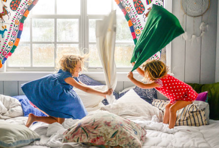 Two young children playing with pillows on a large bed.