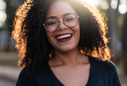 Young woman with curly hair and large glasses smiling at the camera.