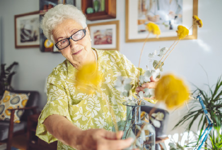 Elderly woman arranging yellow flowers in a vase.