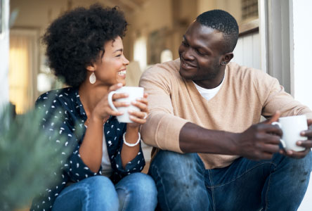 Young couple smiling and sitting together outside while holding coffee mugs.