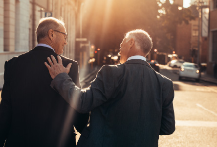 Two older businessmen walking down a street with their backs towards the camera.