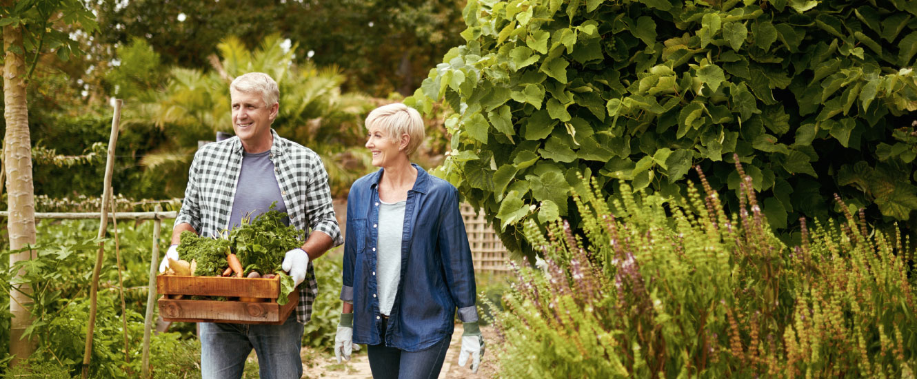 A mature couple walking through in a lush garden.