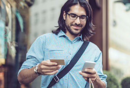 Man with long hair looking down at a smartphone and credit card he is holding.